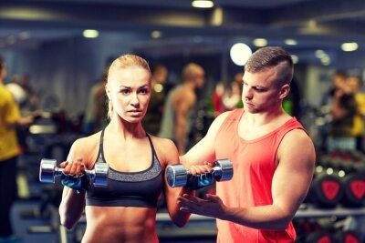 Plakát mladý pár s činky projevil v tělocvičně