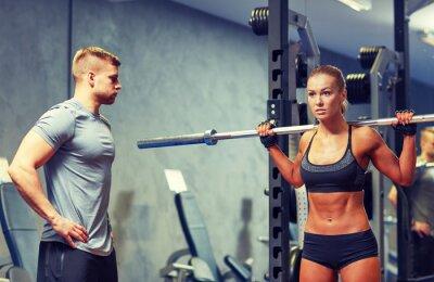 Plakát muž a žena s činka protahování svalů v posilovně