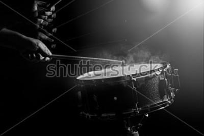 Plakát Muž hraje bubínek v pozadí s nízkým světlem.