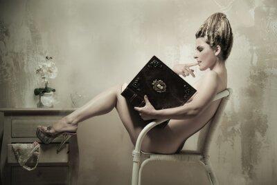 Plakát Nahá žena sedící v křesle s knihou v interiéru