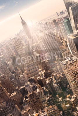 Plakát New York City. Manhattan centrální panorama s osvětlením Empire State Building a mrakodrapy při západu slunce. Vertikální složení. Teplý večer barvy. Sluneční paprsky a odlesk objektivu.