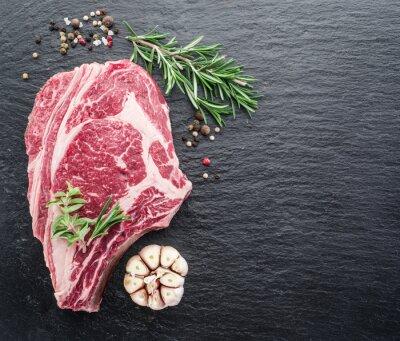 Plakát Rib eye steak s kořením na černém pozadí.