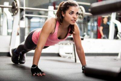 Plakát Roztomilá brunetka pracuje se v tělocvičně