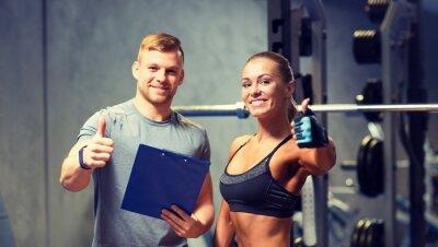 Plakát s úsměvem mladá žena s osobním trenérem v tělocvičně