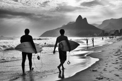 Plakát Scenic černé a bílé pohled na Rio de Janeiru v Brazílii s brazilskou surfaři chůze podél břehu pláže Ipanema