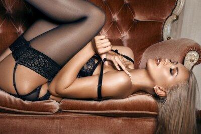 Plakát sexy žena v černém prádle svůdná, ležící na gauči v punčochách