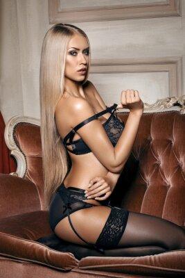 Plakát sexy žena v černém prádle svůdná sedí na gauči v punčochách