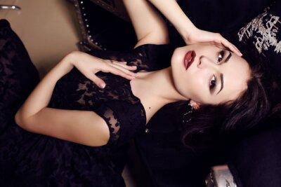 Plakát sexy žena v černých šatech pózuje v luxusním interiérem