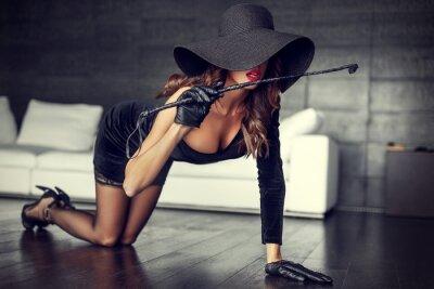 Plakát Sexy žena v klobouku a biče klečí na podlaze krytým
