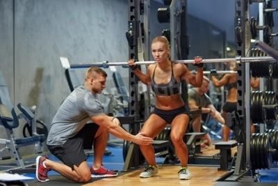 Plakát sport, fitness, týmová práce, kulturistika a lidé koncept - mladá žena a osobní trenér s činka protahování svalů v posilovně