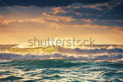 Plakát Sunrise and shining waves in ocean