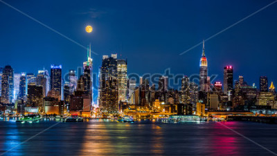 Plakát Super Moon above New York skyline. The top of the Empire State Building is illuminated with the colors of the German and Argentinian flags in honor of the Soccer World Cup final.