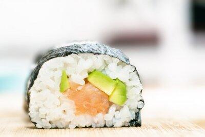 Plakát Sushi s lososem, avokádem, rýže v mořských řasách a hůlky na dřevěném stole