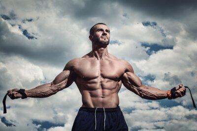 Plakát Svalnatý muž pod zatažené obloze