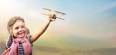 Plakát Svoboda snít - Radostné dítě hraje s letadlem proti obloze