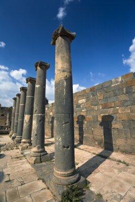 Plakát Sýrie. Bosra. Pozůstatky římských lázní - čedičové sloupy. Toto místo je na seznamu světového dědictví UNESCO