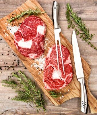 Plakát Syrové čerstvé maso ribeye steak s bylinkami a kořením na dřevěném stole