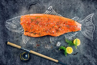 Plakát syrové ryby, losos steak s přísadami, jako je citron, pepř, mořskou solí a koprem na černé desce, nakreslil obraz s křídou lososa ryb s steak a rybářským prutem