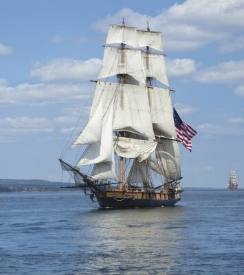 Plakát Tall ship with American flag sailing on blue waters