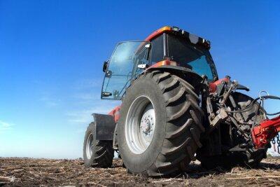 Plakát Traktor pracující v terénu slunečný den