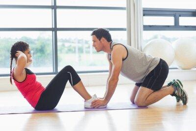 Plakát Trenér pomáhá žena dělat zkracovačky v tělocvičně