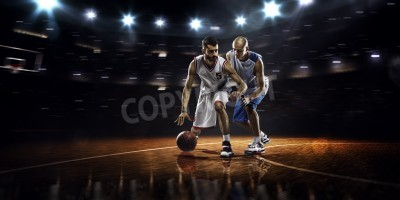 Plakát Two basketball players in action in gym in lights