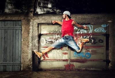 Plakát Young man jumping / dancing on grunge graffiti wall background