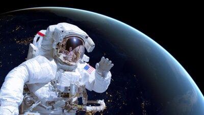 Plakát Zblízka kosmonauta ve vesmíru, země v noci na pozadí. Prvky tohoto obrázku jsou vybaveny NASA