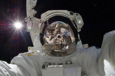 Plakát zblízka pohled na plovoucí astronaut s odrazem ukazující vesmírné stanici (některé prvky NASA)