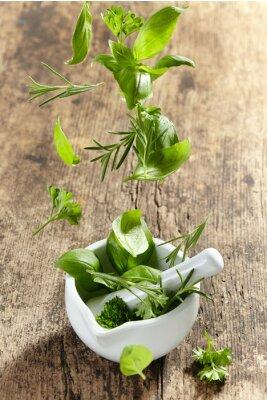 Plakát zelené bylinky, které spadají do malty a paličkou