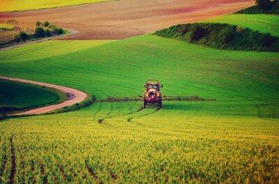 Plakát Zemědělských strojů stříkání insekticid na zelené louce, zemědělské přirozený sezónní jarní pozadí, vintag retro styl hipster