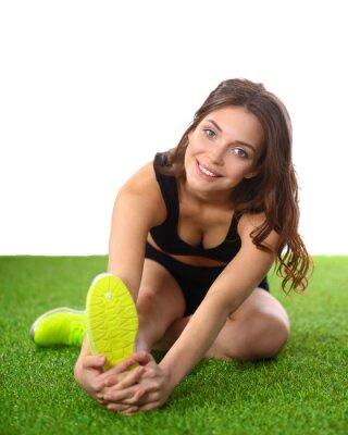 Plakát Žena dělá protahovací cvičení na zelené trávě