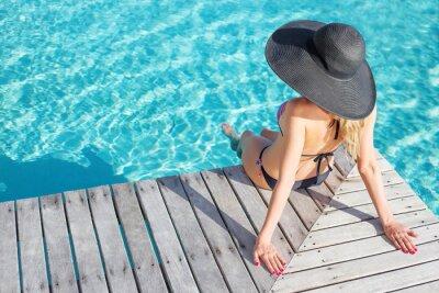 Plakát Žena sedí na palubě u bazénu