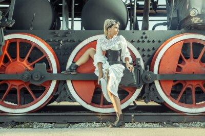 Plakát Žena ve vintage šaty sedí na kole lokomotivy.